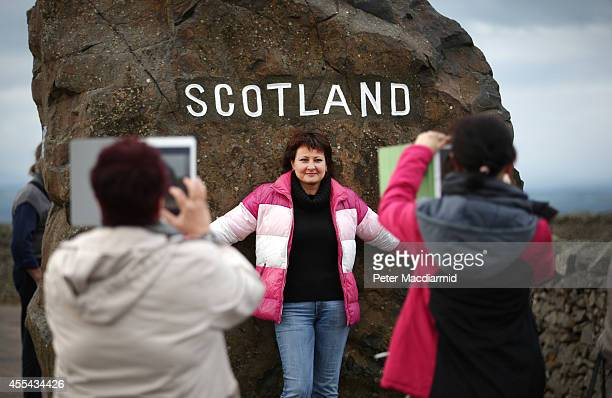 Russian tourists take photographs on the border between England and Scotland on September 14 2014 in Carter Bar Scotland The latest polls in...