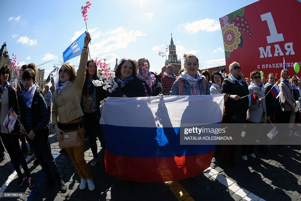 Russian Trade Unions' members holding flags and artificial flowers parade on Red Square in Moscow on May 1, 2016, during their May Day demonstration. / AFP / NATALIA