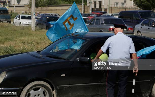 A Russian traffic police officer speaks with Crimean Tatars holding their flags as they sit in a car during a day of Crimean Tatars' national flag in...