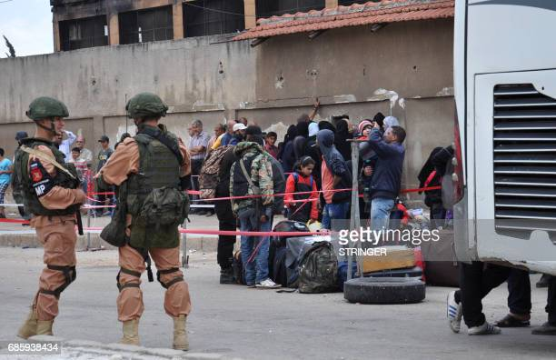 Russian troops stand guard as Syrian opposition fighters and their families board a bus at a checkpoint manned by regime forces ahead of their...