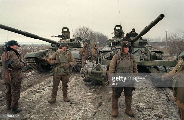 A Russian unit's lead T72 tanks one mounted with a mineclearing system halt near Samashky some 40 kilometers from Grozny on December 13 1994 Russian...
