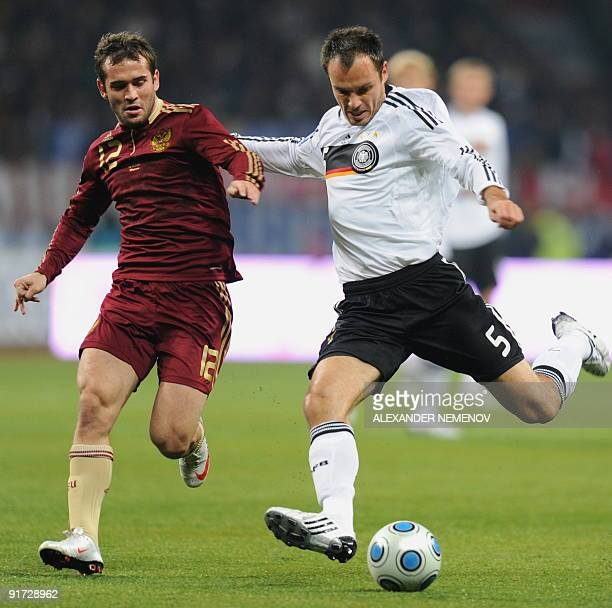 Russian Vladimir Gabulov fights for the ball with German Heiko Westermann in Moscow on October 10 during their European Group Four match World Cup...