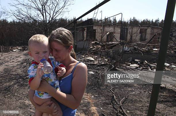 A Russian woman holding a baby cries near the remains of her burnt out home in Voronezh on August 1 2010 Firefighters fought an uphill battle against...