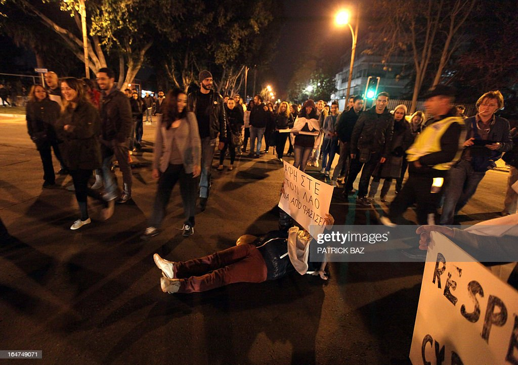 A Russian woman holding Cypriot nationality lies on the ground as protesters block a street leading to the parliament in Nicosia on March 27, 2013. Cyprus confirmed that banks would reopen on March 28, after a nearly two-week lockdown on the bailed-out country, but only under the first capital controls of their kind in the eurozone.