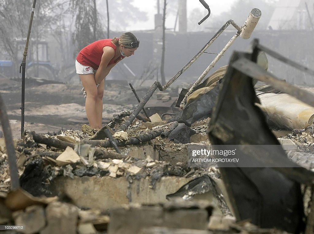 A Russian woman looks around burned house in village Peredelcy on August 7 2010 Russia struggled to contain the worst wildfires in its modern history...