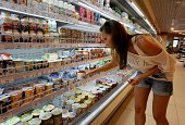 A Russian woman shops for yogurt in Saint Petersburg on August 7 2014 Russia retaliated against tough new Western sanctions banning most food imports...