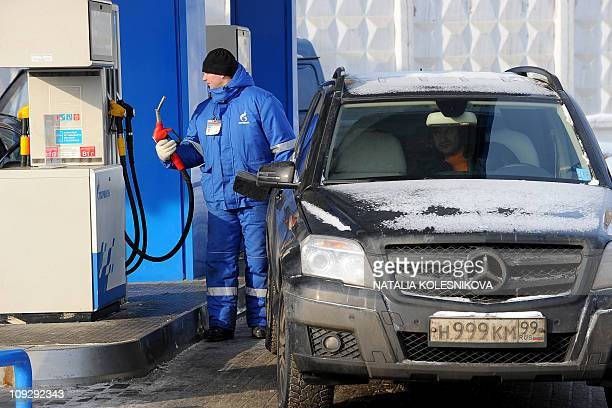 A Russian worker refuels a car at the Gazprom Neft petrol station in Moscow on February 17 2011 AFP PHOTO / NATALIA KOLESNIKOVA