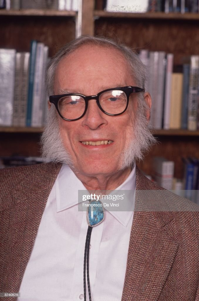 Russianborn American author Isaac Asimov smiling while posing in front of a bookcase