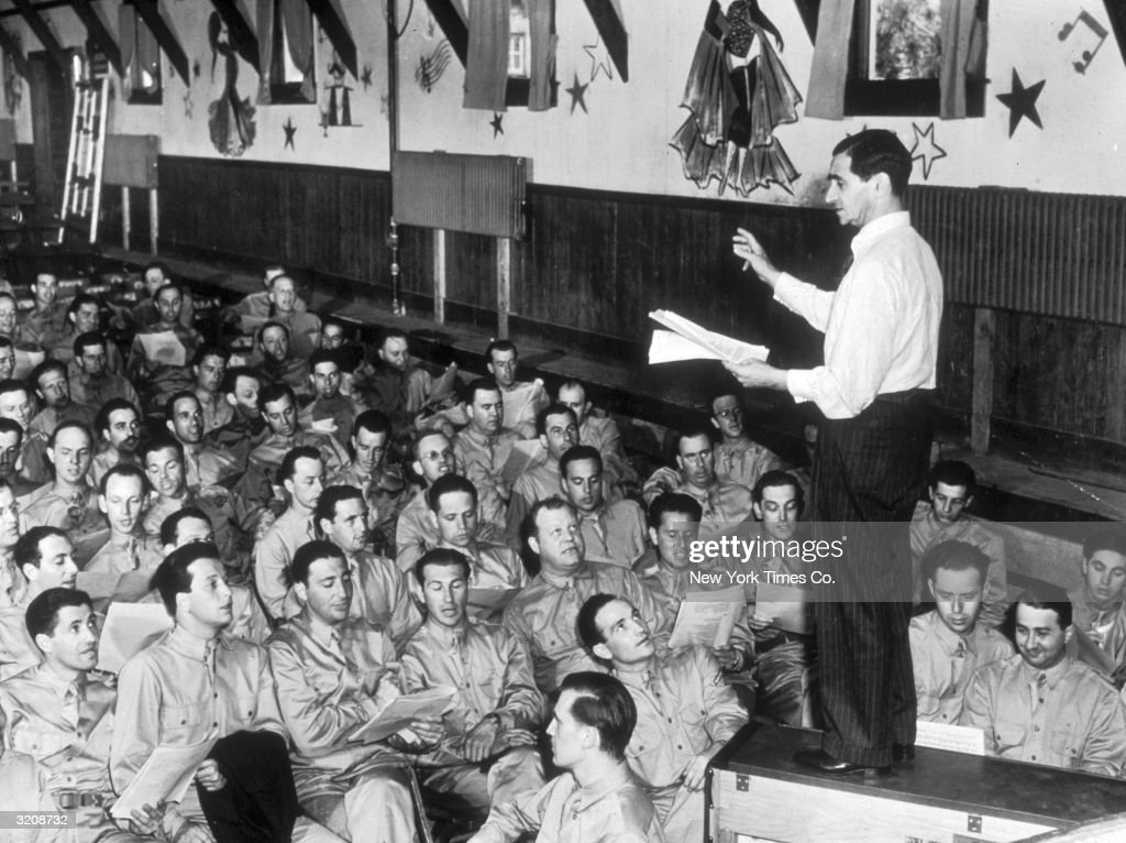 Russian-born composer Irving Berlin (Israel Baline, 1888 - 1989) stands atop a piano, leading a group of American servicemen in rehearsal for his Broadway musical, 'This Is The Army,' Camp Upton, Long Island, New York.