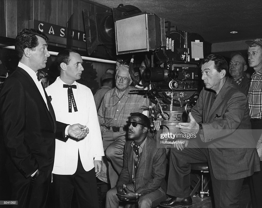 Russian-born director Lewis Milestone (1895 - 1980) talks to American actors (L-R; foreground) Dean Martin (1917 - 1995), Joey Bishop and Sammy Davis Jr. (1925 - 1990) on the set of his film, 'Ocean's Eleven'.