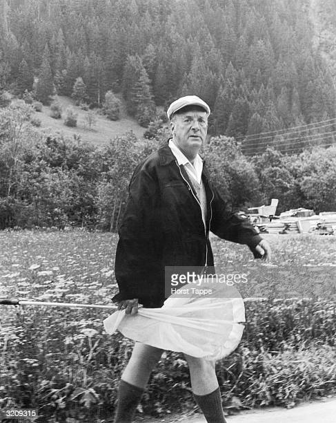 Russianborn writer Vladimir Nabokov carries a net while hunting for butterflies at the foot of a mountain in Switzerland