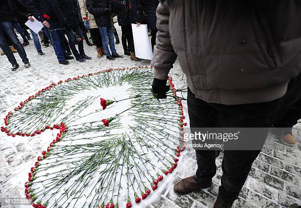 Russians lay flowers in a heartshaped tribute to murdered 'Charlie Hebdo' employees in front of the French embassy in Moscow Russia on 09 January...