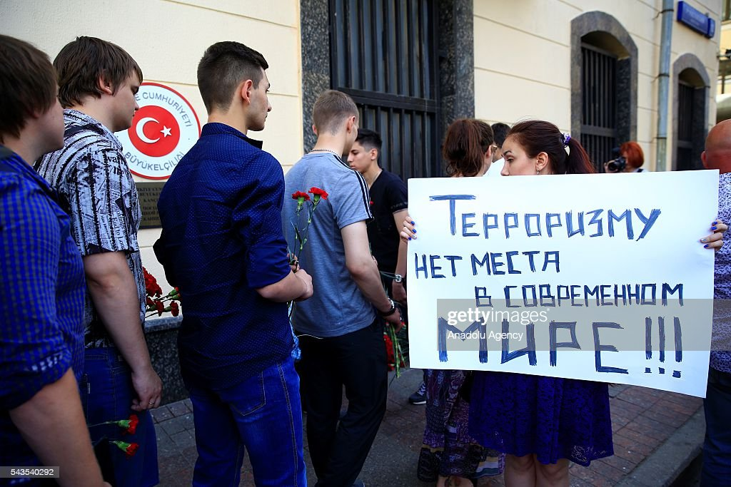 Russians leave flowers for the victims of the terrorist attack at Ataturk International Airport as a woman holds a banner reading in 'Our condolences to Turkey' outside the Turkish Embassy in Moscow, Russia on June 29, 2016. The death toll in Istanbuls airport terror attack has risen to 41, the regional governors office said Wednesday.