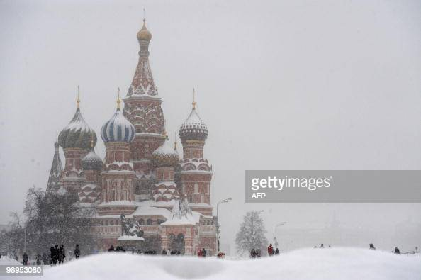 Russians walk near St Basil's Cathedral under heavy snowfall on Red Square in Moscow on February 22 2010 Moscow is seeing record snowfall for the...