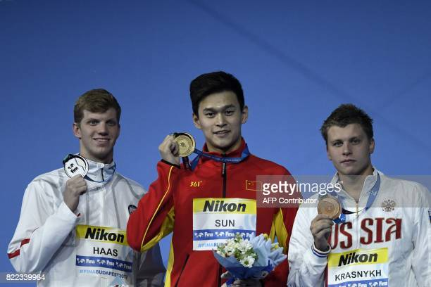 Russia's Aleksandr Krasnykh China's Sun Yang and US Townley Haas celebrate on the podium after the men's 200m freestyle final during the swimming...