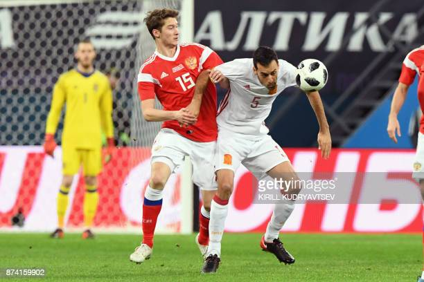 Russia's Aleksey Miranchuk and Spain's midfielder Sergio Busquets vie for the ball during an international friendly football match between Russia and...