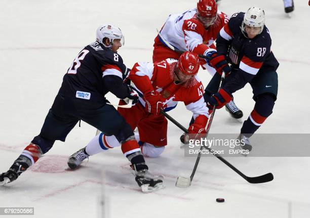 Russia's Alexander Radulov is tackled by USA's Joe Pavelski and Kane Patrick in their Preliminary Round match during the 2014 Sochi Olympic Games in...