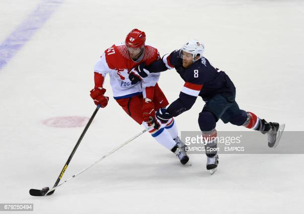 Russia's Alexander Radulov is tackled by USA's Joe Pavelski in their Preliminary Round match during the 2014 Sochi Olympic Games in Krasnaya Polyana...