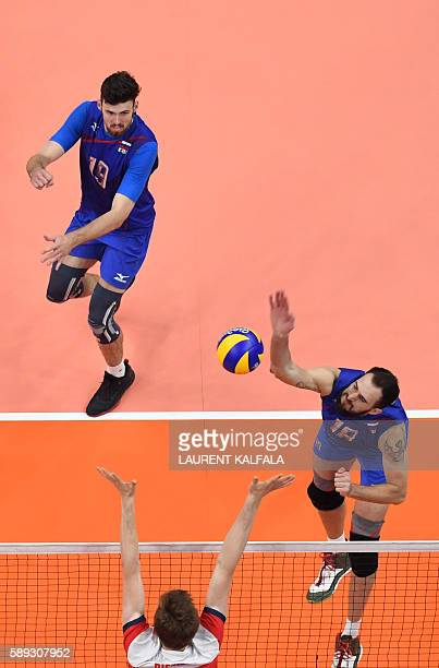 Russia's Alexander Volkov spikes the ball during the men's qualifying volleyball match between Poland and Russia at the Maracanazinho stadium in Rio...