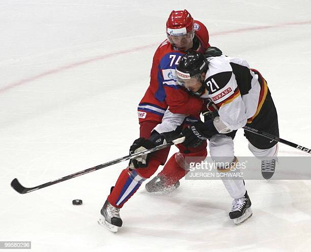 Russia's Alexei Emelin vies with Germany's John Tripp during the IIHF Ice Hockey World Championship match Russia vs Germany in the western German...