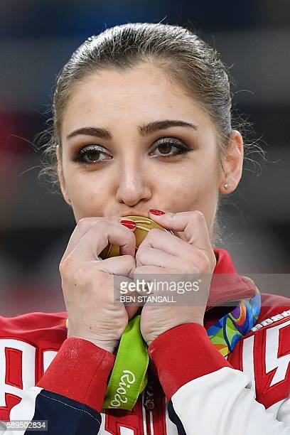 Russia's Aliya Mustafina celebrates with her gold medal on the podium of the women's uneven bars event final of the Artistic Gymnastics at the...