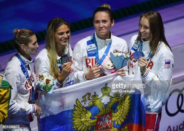 Russia's Anastasiia Fesikova Russia's Yuliya Efimova Russia's Svetlana Chimrova and Russia's Veronika Popova celebrate on the podium aafter the final...