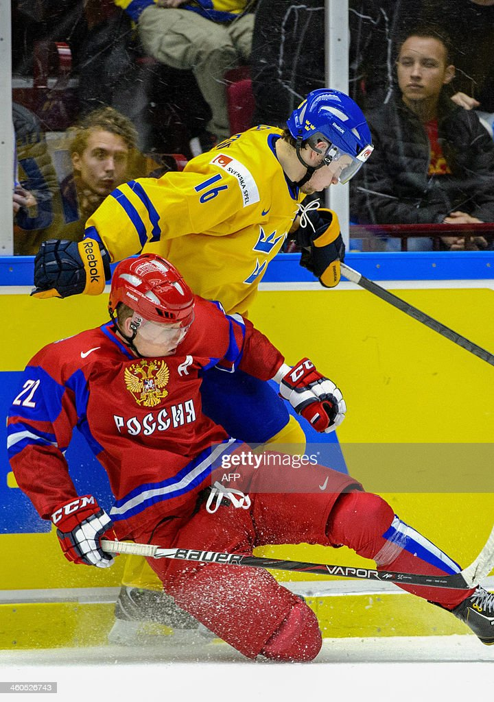Russia's Andrei Mironov (front) is checked by Sweden's Filip Forsberg during the World Junior Hockey Championships semifinal between Sweden and Russia at Malmo Arena in Malmo, Sweden on January 4, 2014.