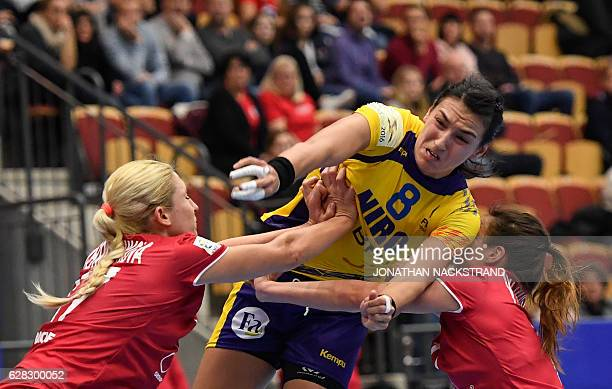 Russia's Anna Vyakhireva and Vladlena Bobrovnikova try to stop Romania's Cristina Neagu as she throws the ball during the Women's European Handball...