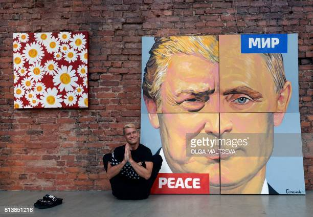Russia's artist Alexey Sergienko poses next to his artwork depicting US President Donald Trump and Russian President Vladimir Putin in Saint...