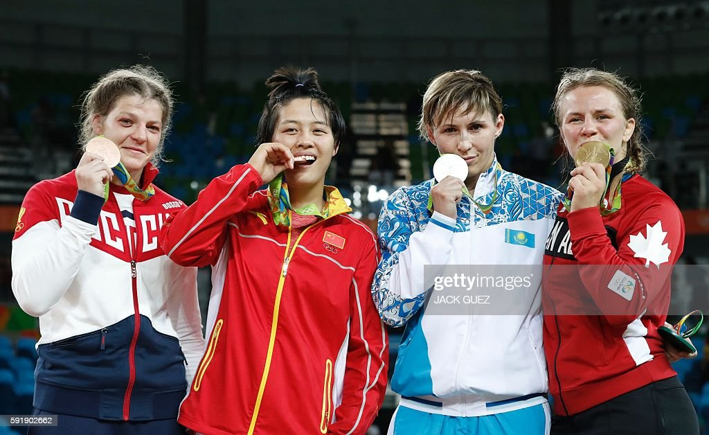 Russia's bronze medallist Ekaterina Bukina, China's bronze medallist Zhang Fengliu, Kazakhstan's silver medallist Guzel Manyurova and Canada's gold medallist Erica Elizabeth Wiebe celebrate on the podium at the end of the women's 75kg freestyle wrestling event at the Carioca Arena 2 in Rio de Janeiro on August 18, 2016, during the Rio 2016 Olympic Games. / AFP / Jack GUEZ