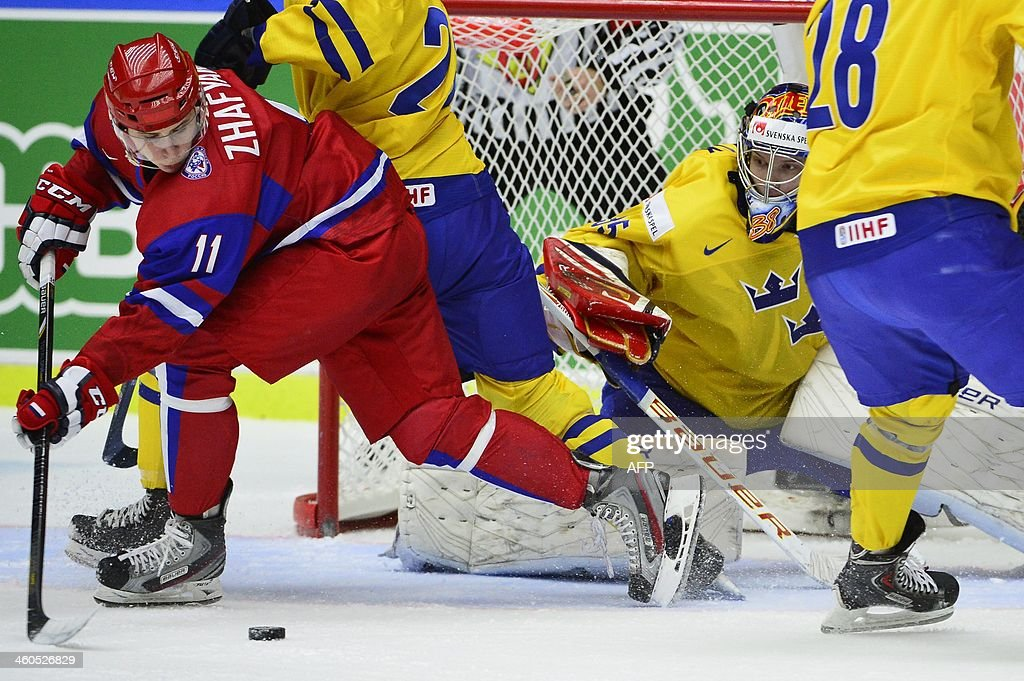 Russia's Damir Zhafyarov (L) tries to find an opening against Sweden's goalkeeper Oscar Dansk during the World Junior Hockey Championships semifinal between Sweden and Russia at Malmo Arena in Malmo, Sweden on January 4, 2014.