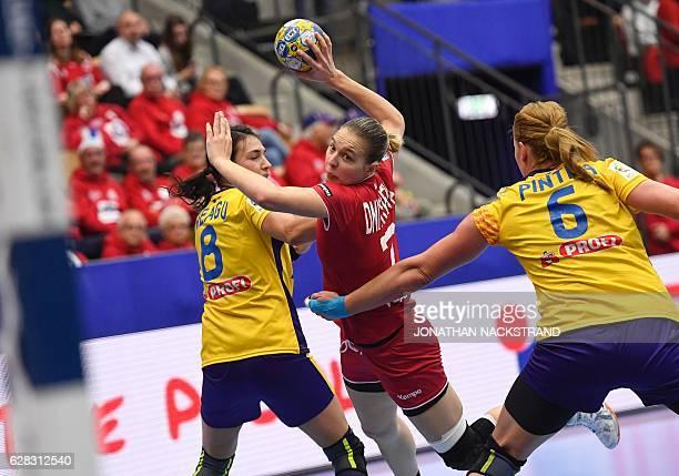 Russia's Daria Dmitrieva prepares to throw the ball between Romania's Cristina Neagu and Crina Elena Pintea during the Women's European Handball...