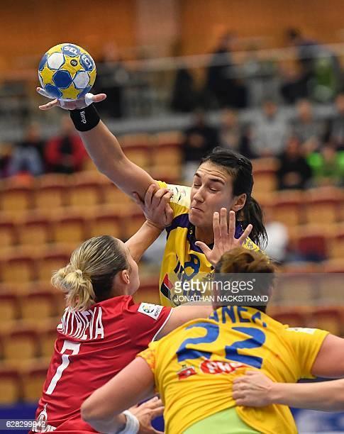 Russia's Daria Dmitrieva tries to stop Romania's Cristina Neagu as she passes the ball to her teammate Oana Manea during the Women's European...
