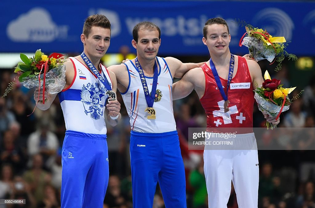 Russias David Belyavskiy (2nd), Armenias Harutyun Merdinyan (1st) and Switzerlands Christian Baumann (3rd) celebrate on the podium after the Mens Pommel Horse competition of the European Artistic Gymnastics Championships 2016 in Bern, Switzerland on May 29, 2016. / AFP / FABRICE