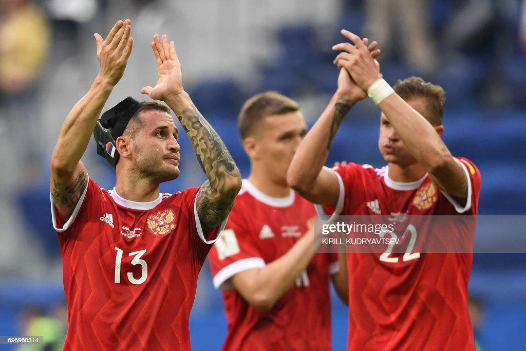 TOPSHOT - Russia's defender Fedor Kudryashov (L) and Russia's midfielder Dmitry Tarasov (R) acknowledge the fans after their 2-0 win against New Zealand in the 2017 Confederations Cup group A football match between Russia and New Zealand at the Krestovsky Stadium in Saint-Petersburg on June 17, 2017. / AFP PHOTO / Kirill KUDRYAVTSEV