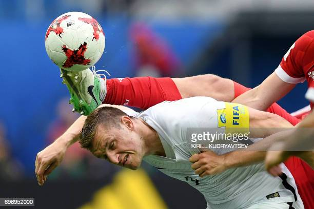 TOPSHOT Russia's defender Georgiy Dzhikiya tackles New Zealand's forward Chris Wood for the ball during the 2017 Confederations Cup group A football...