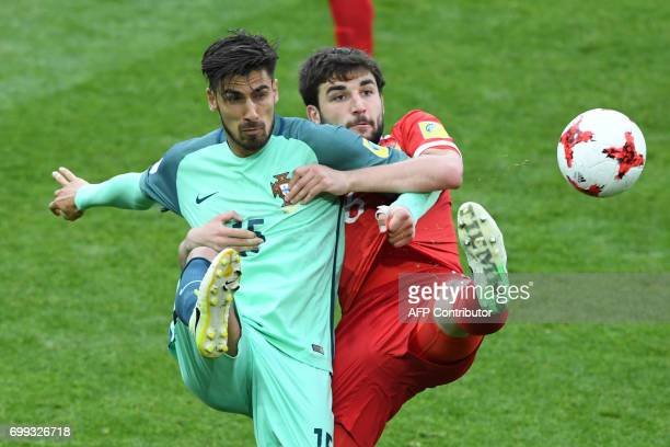 TOPSHOT Russia's defender Georgiy Dzhikiya vies with Portugal's midfielder Andre Gomes during the 2017 Confederations Cup group A football match...