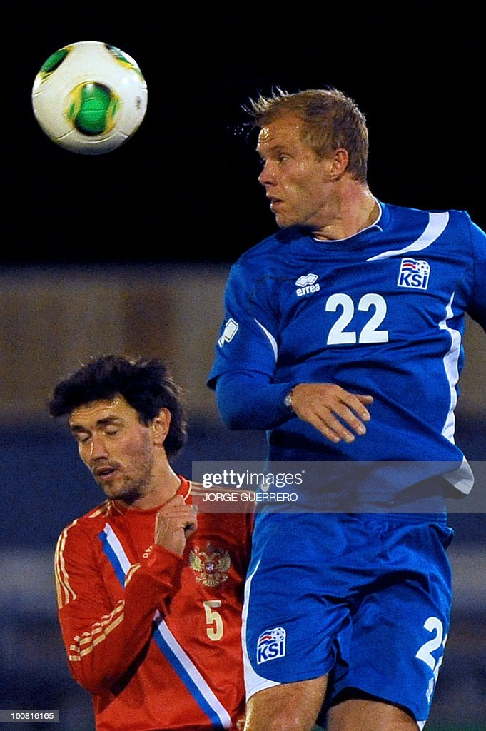 Russia's defender Yuri Zhirkov (L) vies with Iceland's forward Eidur Smari Gudjohnsen during the international friendly football match Iceland vs Russia at the municipal stadium in Marbella on February 6, 2013.