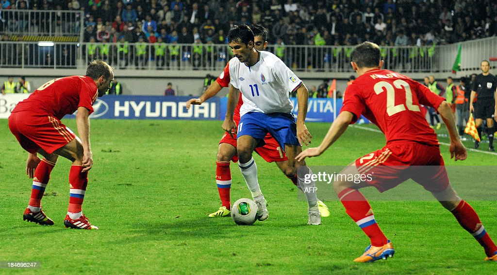 Russia's Denis Glushakov (L) and Alexey Kozlov (R) fight for the ball with Azerbaijan's Rauf ALiyev (C) on October 15, 2013 during a FIFA 2014 World Cup qualifying football match in Baku.