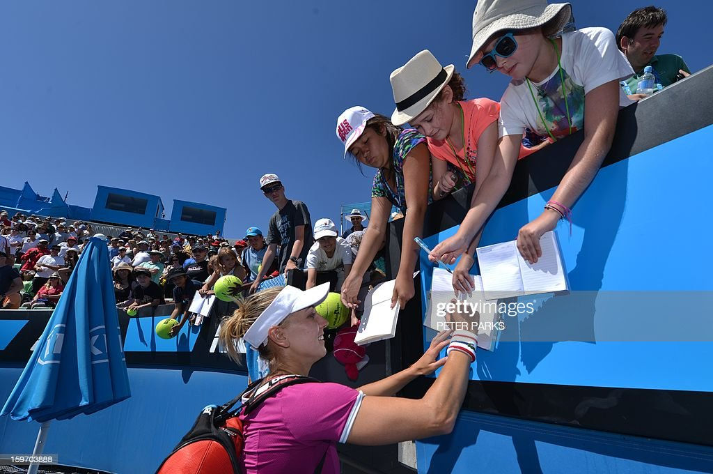 Russia's Elena Vesnina signs autographs after her victory against Italy's Roberta Vinci during their women's singles match on day six of the Australian Open tennis tournament in Melbourne on January 19, 2013. AFP PHOTO / PETER PARKS IMAGE STRICTLY RESTRICTED TO EDITORIAL USE - STRICTLY NO COMMERCIAL USE