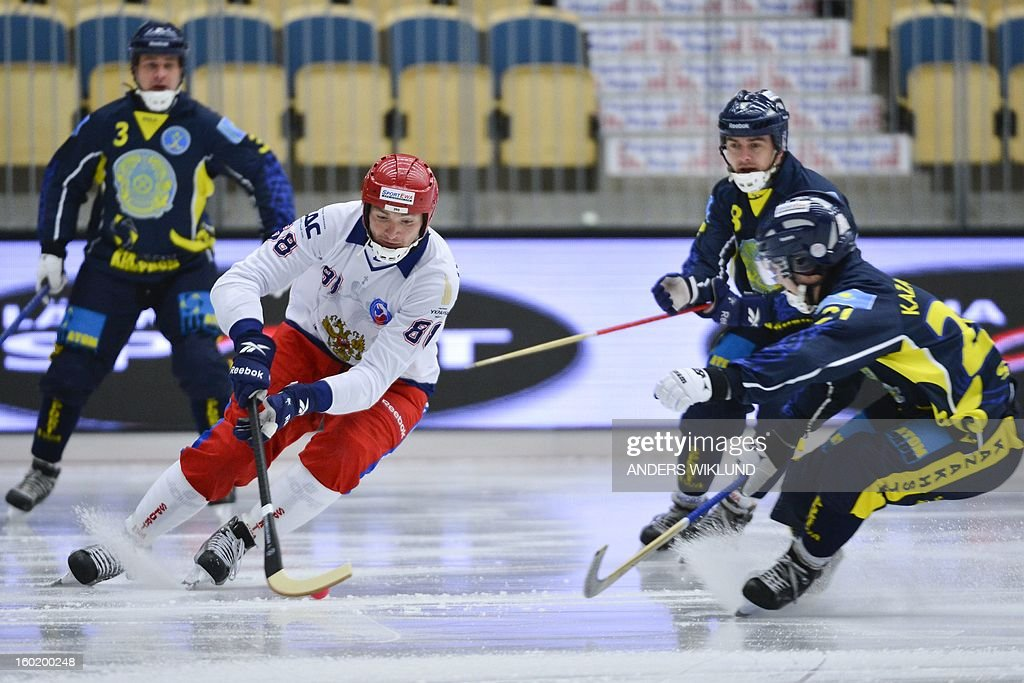 Russia's Evegeny Ivanushkin (C) is chased by Kazakhstans Ryslan Galyutdinov (R) during the Bandy World Championship match between Russia and Kazakhstan in Vanersborg, Sweden, on January 27, 2013.