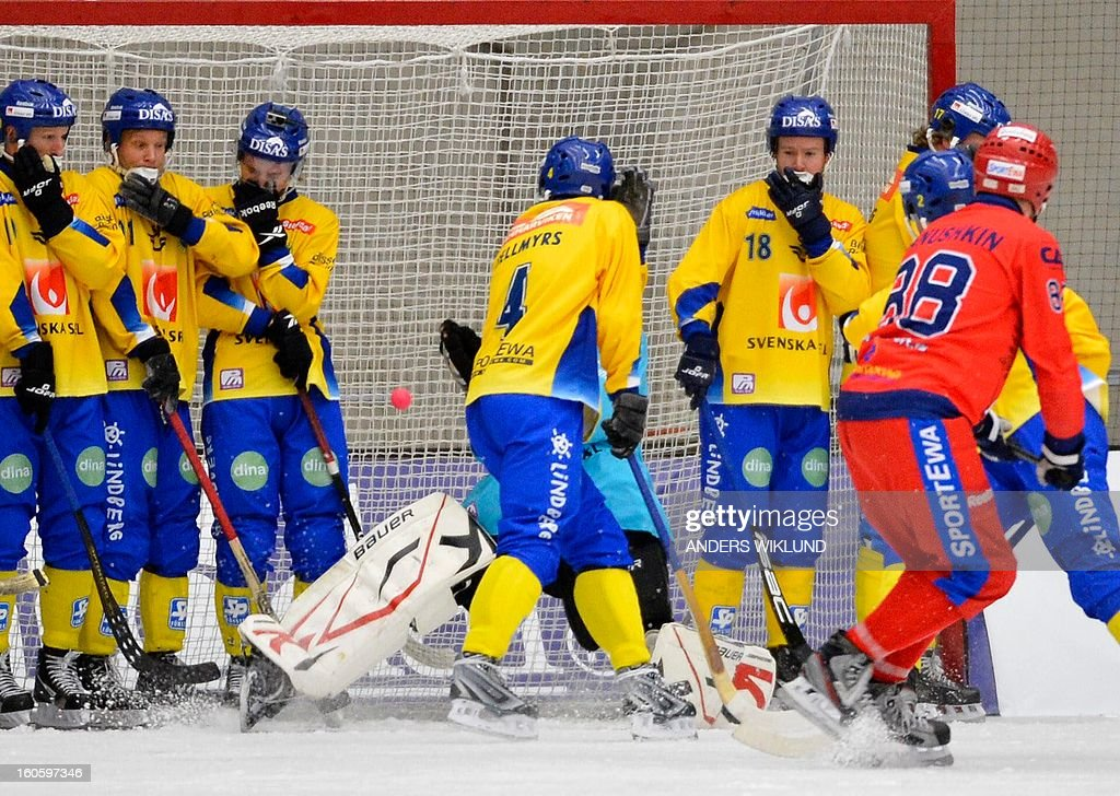 Russia's Evgeny Ivanushkin (R) scores the 2-1 goal past Sweden's players during Bandy World Championship final match Sweden vs Russia in Vanersborg, Sweden, February 3, 2013.