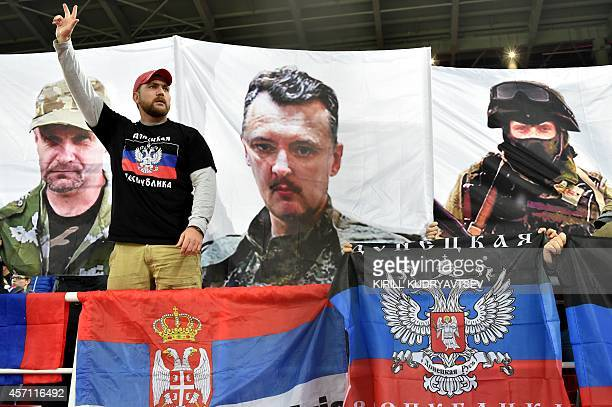 A Russia's fan gestures in front of flags of Russia Serbia and the selfproclaimed Donetsk People's Republic and banners showing portraits of...