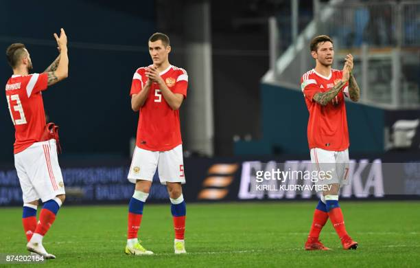 Russia's Fedor Kudryashov Viktor Vasin and Fedor Smolov greet supporters after an international friendly football match between Russia and Spain at...