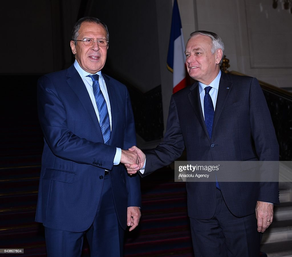 Russia's Foreign Minister Sergey Lavrov (L) and French Foreign Minister Jean-Marc Ayrault (R) shake hands as they pose for a photograph after their meeting in Paris, France on June 29, 2016.
