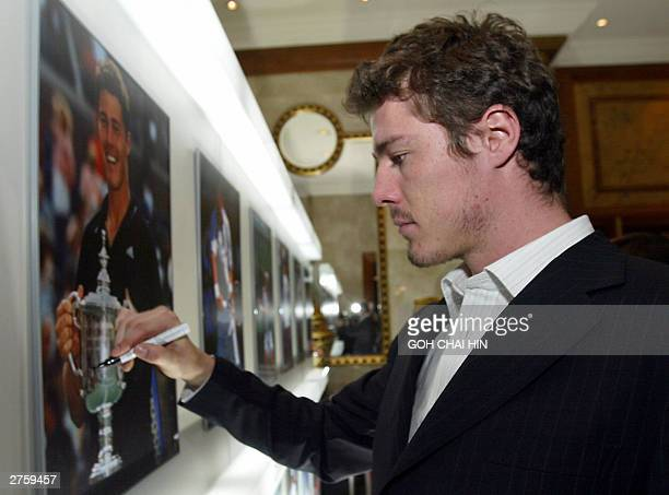Russia's former World number one Marat Safin who is recovering from an injury autographs a photo of himself in action which is on display at a...