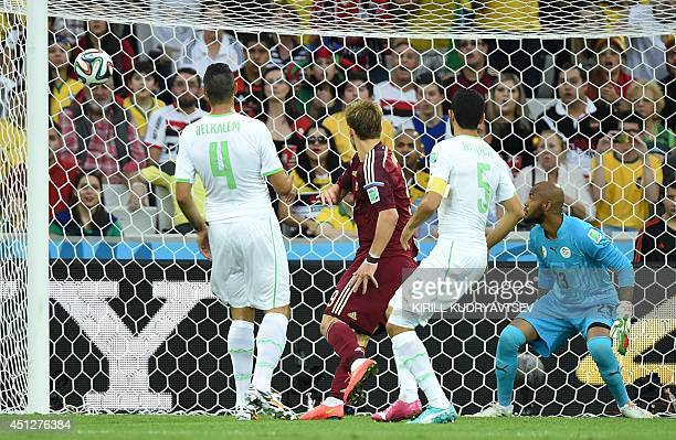 Russia's forward Alexander Kokorin scores his team's first goal past Algeria's goalkeeper Rais Mbohli as Algeria's defender Essaid Belkalem and...