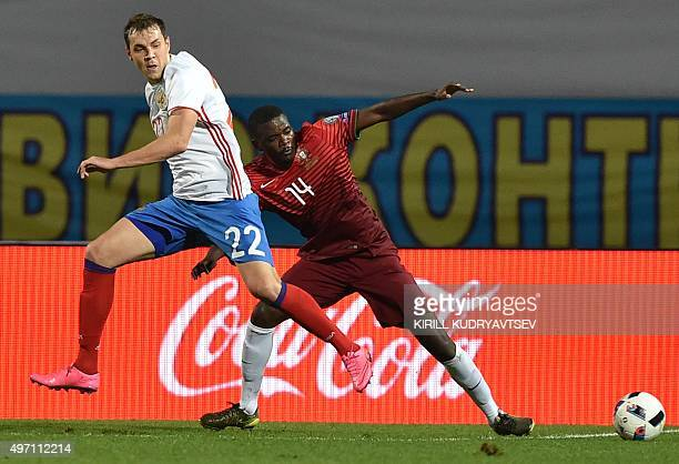 Russia's forward Artem Dzyuba vies for the ball with Portugal's midfielder William Carvalho during the friendly football match between Russia and...