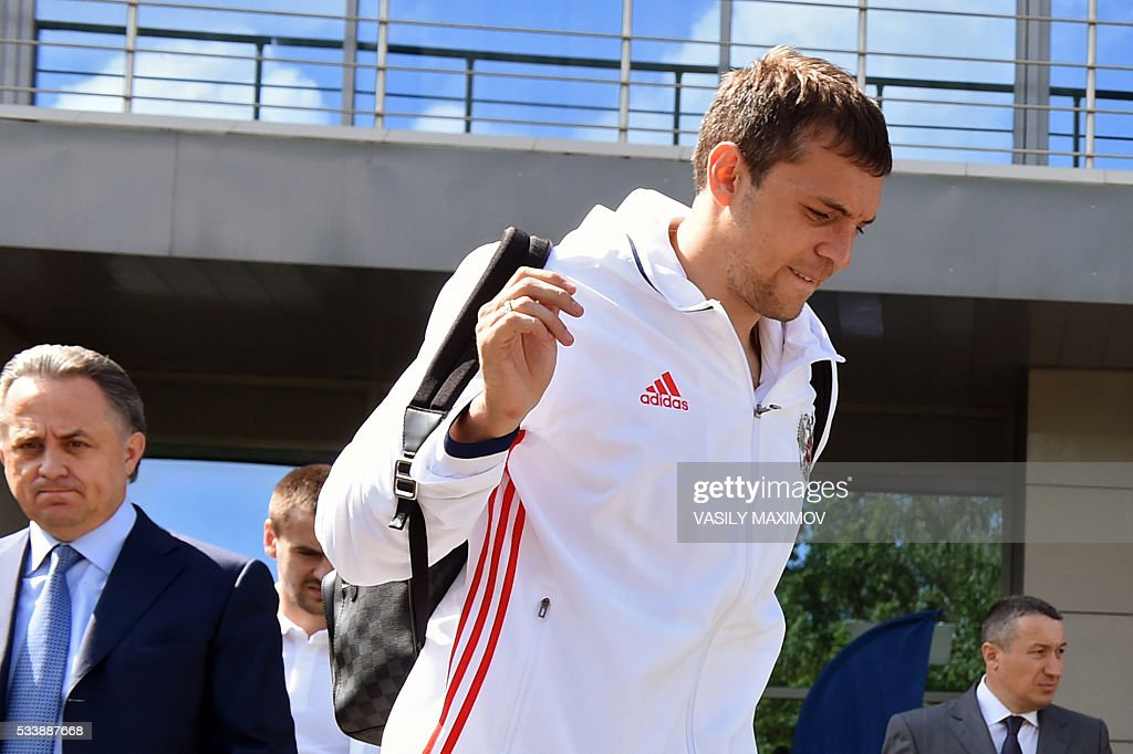Russia's forward Artem Dzyuba walks past the country's sports minister Vitaly Mutko as he boards a bus before the team's departure at Moscow?'s Sheremetyevo airport on May 24, 2016. Russia?'s footballers departed from Moscow to Switzerland where they are scheduled to play two friendly games before their trip to France where they are to take part in the UEFA European Championship. / AFP / VASILY