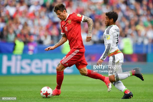 Russia's forward Fedor Smolov fights for the ball against Mexico's midfielder Jonathan Dos Santos during the 2017 Confederations Cup group A football...
